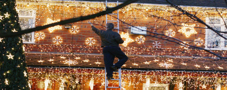 man on ladder hanging Christmas lights