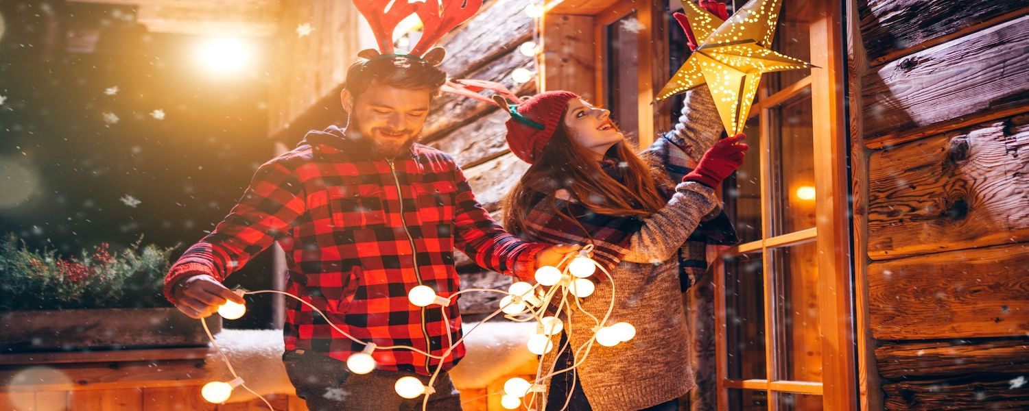 man and woman stringing outdoor Christmas lights